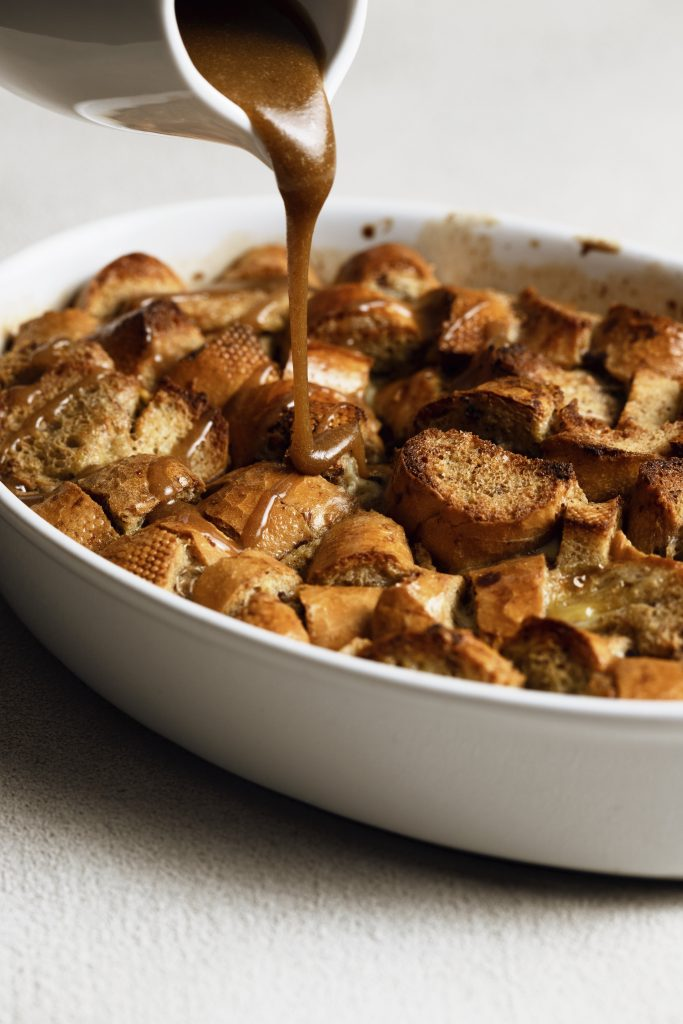 Easy baked french toast casserole atop a table with homemade caramel sauce being drizzled onto it out of a white creamer dish.