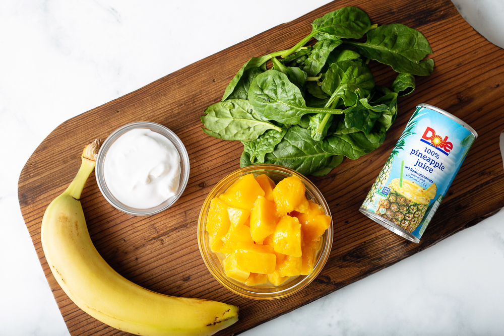 Ingredients for mango pineapple green smoothie laid atop a rustic cutting board. Ingredients include banana, coconut milk, mango, pineapple juice, and fresh spinach.