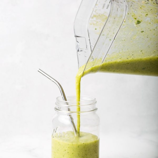 Bright green mango pineapple spinach smoothie being poured from a ninja blender into a mason jar with a metal reuseable straw, on a white background.
