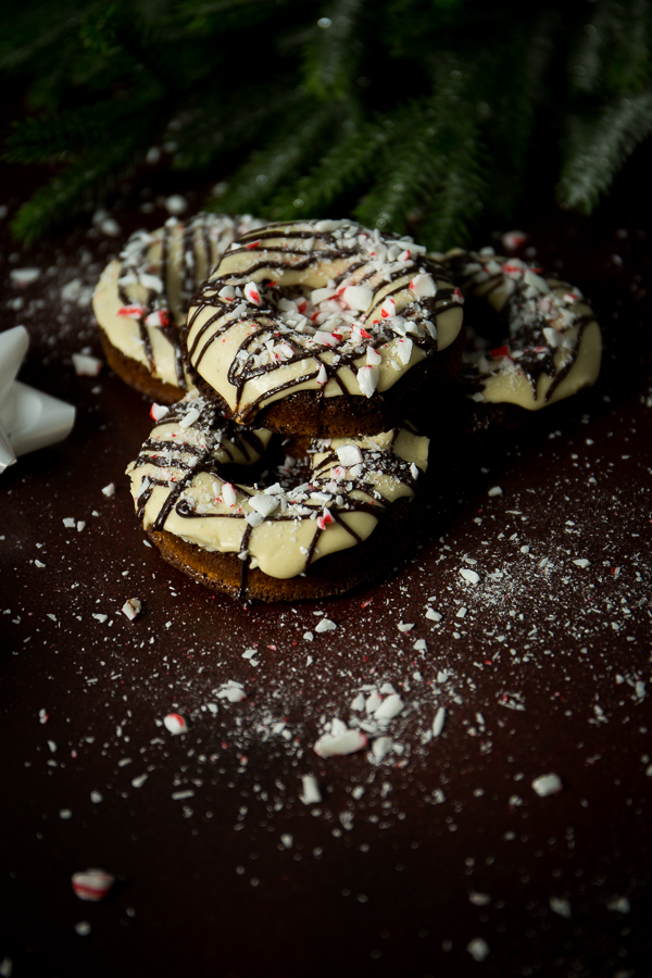 Eggnog gluten-free donuts drizzled with milk-chocolate and peppermint candy, sit atop a maroon background with holiday decor.
